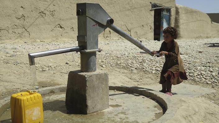 Balkh, village de Wocha Wona. La jeune Raaziqa, âgée de 6 ans, pompe de l'eau. Balkh, Wocha Wona village. Six-year-old Raaziqa draws water from a borehole.