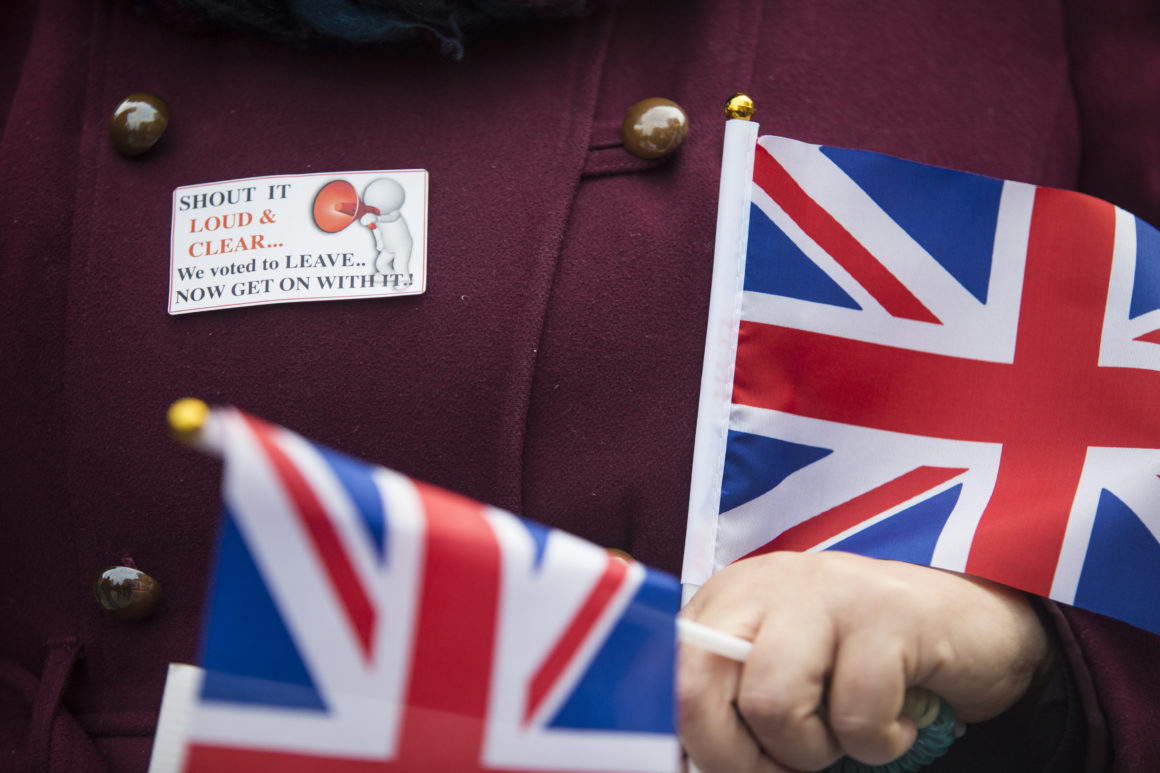 """LONDON, ENGLAND - NOVEMBER 23: A pro-Brexit demonstrator holds Union Jack flags during a protest outside the Houses of Parliament on November 23, 2016 in London, England. British Prime Minister Theresa May has said that she will not delay triggering article 50, the formal process of leaving the European Union, but wants to avoid a """"cliff edge"""". (Photo by Jack Taylor/Getty Images)"""