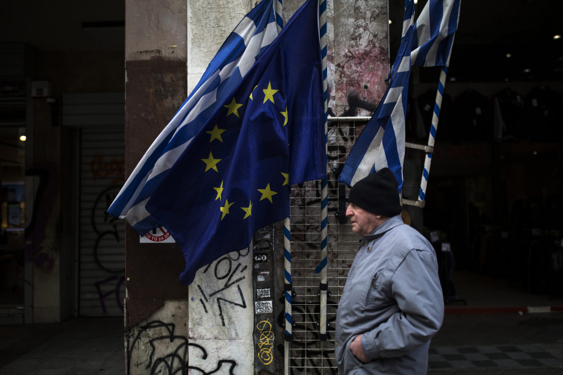 """A man walks past Greek and an EU flags in Athens on February 11, 2017. Greek Prime Minister Alexis Tsipras on February 11, 2017 warned the International Monetary Fund and German Finance Minister Wolfgang Schaeuble to """"stop playing with fire"""" in the handling of his country's debt. / AFP / Angelos Tzortzinis (Photo credit should read ANGELOS TZORTZINIS/AFP/Getty Images)"""