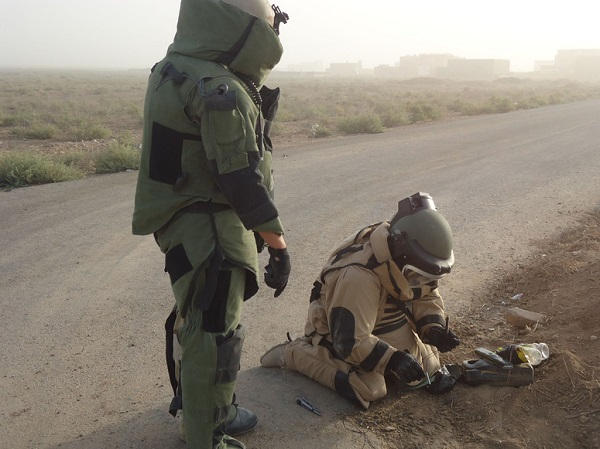 Two Iraqi EOD operators prepare to dispose of a partially disassembled IED. The device will be detonated on the spot by placing the block of plastic explosives C-4 on top of the main explosive charge and initiating it remotely.