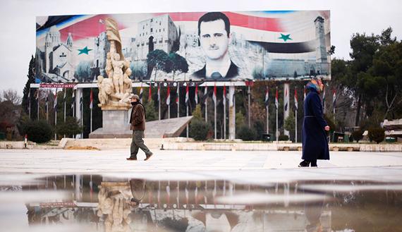 People walk past a billboard depicting Syria's President Bashar al-Assad at Saadallah al-Jabri Square, in the government controlled area of Aleppo, Syria December 17, 2016. REUTERS/Omar Sanadiki - RTX2VGTH