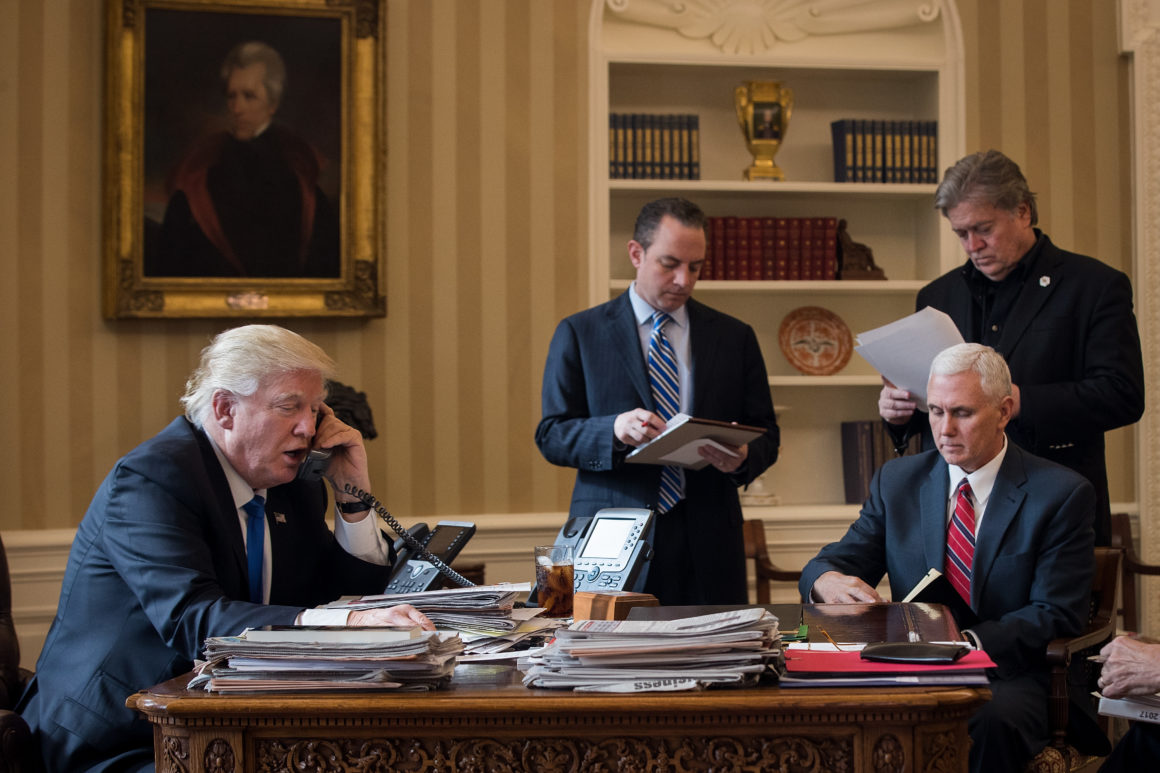 WASHINGTON, DC - JANUARY 28: President Donald Trump speaks on the phone with Russian President Vladimir Putin in the Oval Office of the White House, January 28, 2017 in Washington, DC. Also pictured, from left, White House Chief of Staff Reince Priebus, Vice President Mike Pence, and White House Chief Strategist Steve Bannon. On Saturday, President Trump is making several phone calls with world leaders from Japan, Germany, Russia, France and Australia. (Photo by Drew Angerer/Getty Images)