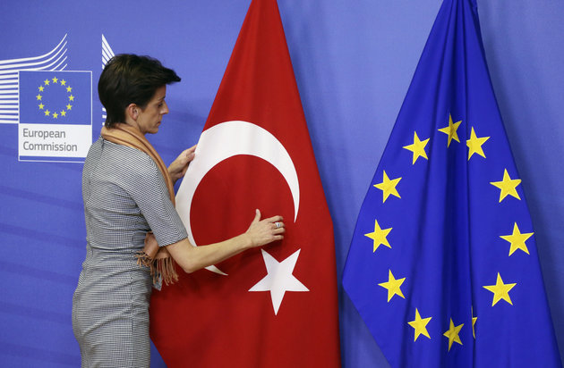 A woman adjusts the Turkish flag next to the European Union flag before the arrival of Turkish Prime Minister Ahmet Davutoglu (unseen) at the EU Commission headquarters in Brussels January 15, 2015. REUTERS/Francois Lenoir (BELGIUM - Tags: POLITICS)