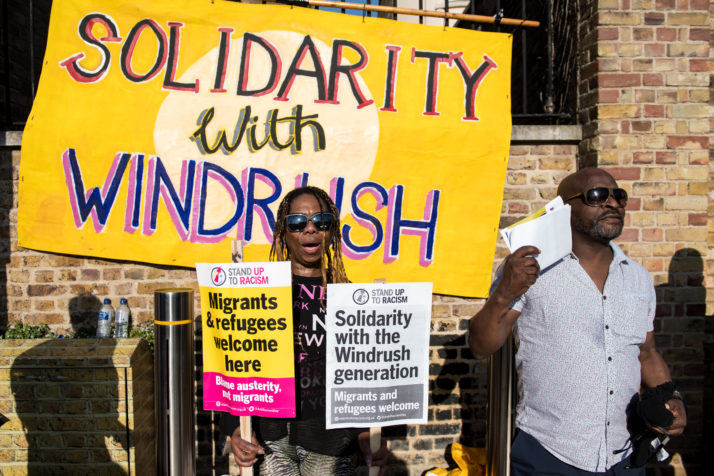 LONDON, ENGLAND - APRIL 20: Demonstrators chant and hold placards during a protest in support of the Windrush generation in Windrush Square, Brixton on April 20, 2018 in London, England. The Windrush generation are people who arrived in the UK after the Second World War from Caribbean countries at the invitation of the British government. It is now thought that an estimated 50,000 people of the Windrush generation face the risk of deportation if they never formalised their residency status and do not have the required documentation to prove it. (Photo by Chris J Ratcliffe/Getty Images)