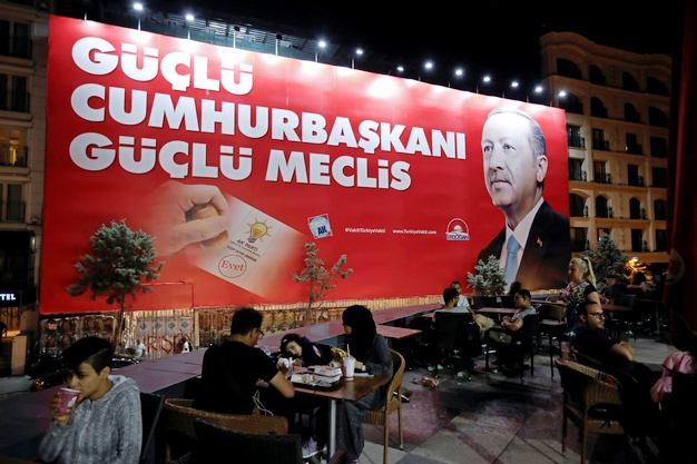 """People sit in a restaurant terrace as a pre-election poster depicting Turkish President Tayyip Erdogan reads """"Strong President, strong parliament"""", in Istanbul, Turkey, June 20, 2018. REUTERS/Alkis Konstantinidis - RC191E4B07A0"""