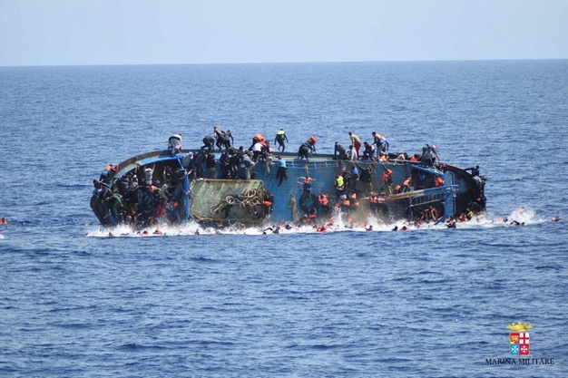 """Migrants are seen on a capsizing boat before a rescue operation by Italian navy ships """"Bettica"""" and """"Bergamini"""" off the coast of Libya in this handout picture released by the Italian Marina Militare on May 25, 2016. Marina Militare/Handout via REUTERS    ATTENTION EDITORS - THIS PICTURE WAS PROVIDED BY A THIRD PARTY. FOR EDITORIAL USE ONLY.   - RTSFVIP"""