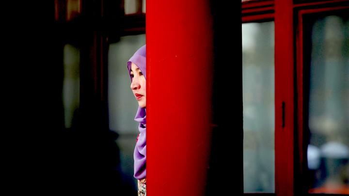 A woman stands behind a pillar during the Eid al-Adha festival at Niujie mosque in Beijing, China September 12, 2016. REUTERS/Jason Lee - D1BEUAVHGQAA