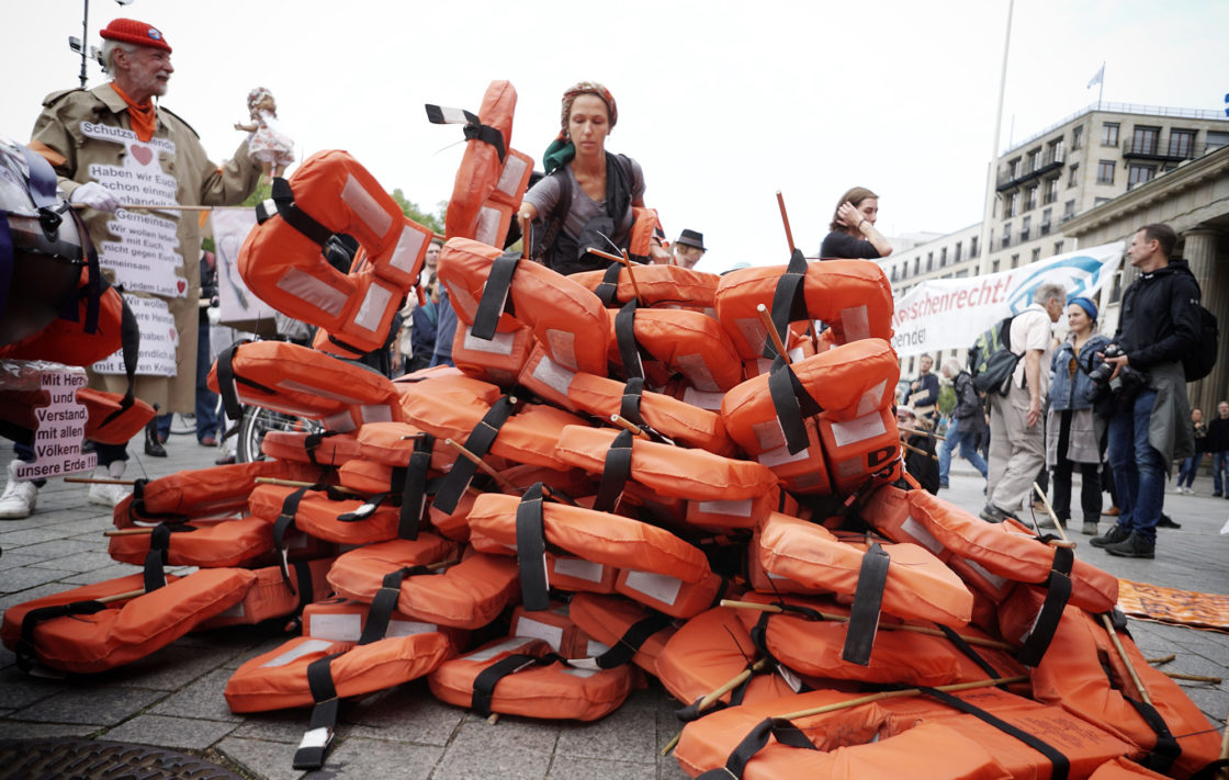 """Supporters of the Seebruecke (sea bridge) movement pile up life vests during a demonstration for unhampered sea rescue of refugees in the Mediterranean Sea and for secure escape routes for migrants that was titled """"Seebruecke creates safe harbours"""" on September 2, 2018 in front of the Brandenburg Gate in Berlin, Germany. (Photo by Kay Nietfeld / dpa / AFP) / Germany OUT (Photo credit should read KAY NIETFELD/AFP/Getty Images)"""