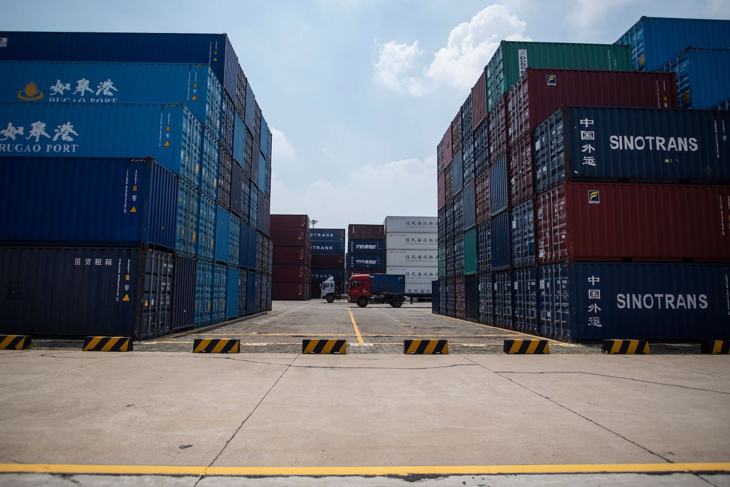 This photo taken on August 7, 2018 shows a truck (C) transporting a container next to stacked containers at a port in Zhangjiagang in China's eastern Jiangsu province. - China's trade surplus with the United States eased in July, when President Donald Trump imposed stiff tariffs on billions of dollars worth of Chinese goods in a showdown between the world's two biggest economies. The figures on August 8 come as the two exchange threats of further measures, which have fuelled fears of a trade war many observers warn could hammer global business. (Photo by Johannes EISELE / AFP) (Photo credit should read JOHANNES EISELE/AFP/Getty Images)