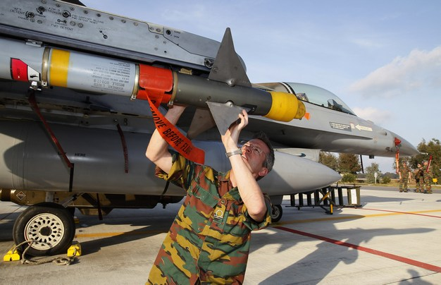 A Belgian army staff member looks at a AIM-9M air-to-air missile attached on a Belgian Air Force F16 fighter aircraft, which is taking part in an offensive in Libya, at Araxos airbase, Greece March 28, 2011. A Libyan rebel spokesman said Muammar Gaddafi's hometown of Sirte had been captured by the rebels on Monday, but no independent verification of the statement was immediately available.     REUTERS/Yves Herman (GREECE - Tags: CONFLICT POLITICS MILITARY) - GM1E73T01RY01